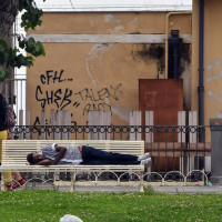 A young migrant sleeps on a bench outside the railway station in Catania, Sicily. JRS Italy known locally as Centro Astalli provides services to asylum seekers in Catania on a daily basis. Credit: JRS Europe/ Oscar Spooner